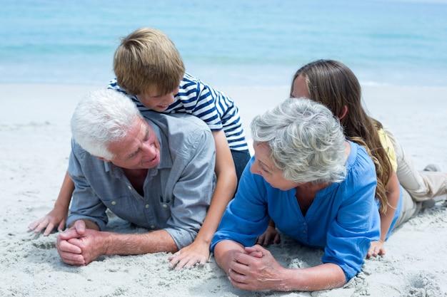 海岸で祖父母に横たわっている子供