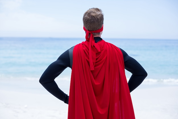 海岸で腰に手を持つスーパーヒーローの衣装