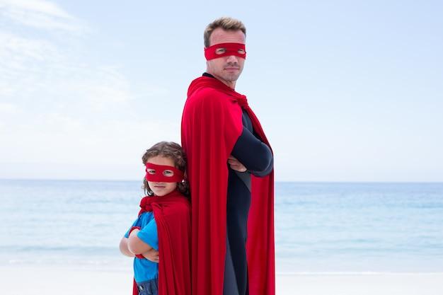 自信を持って男と息子が背中合わせに立っています。