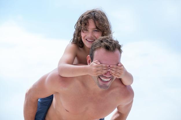 ビーチで父に乗って目を覆っている息子