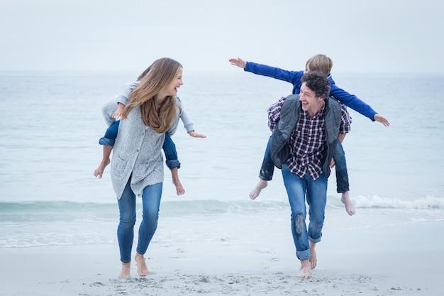 幸せな母と父がビーチで子供たちを運ぶ