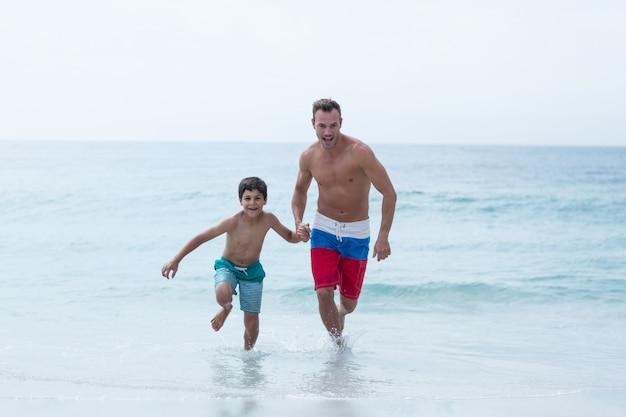 ビーチで走っている父と息子の全長