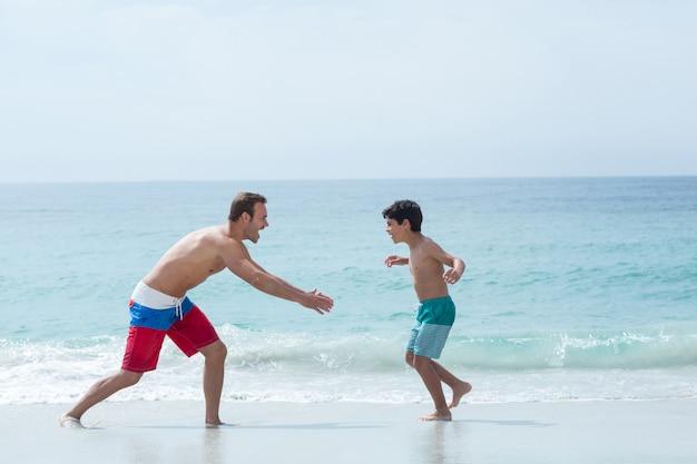 ビーチで息子を追いかけて父