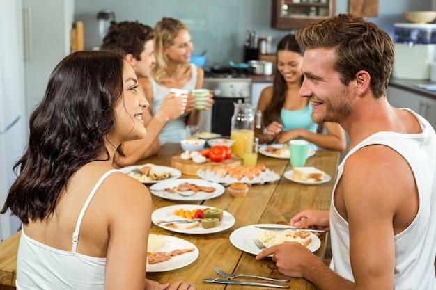 朝食をとりながらお互いを見て笑顔のカップル