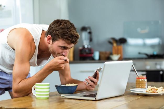 キッチンで携帯電話を使用しながら朝食を持っている人