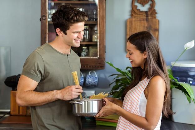 Счастливая молодая пара приготовления пищи на кухне