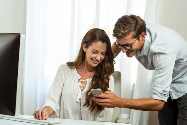 オフィスの机で携帯電話を使用して男性と女性の同僚