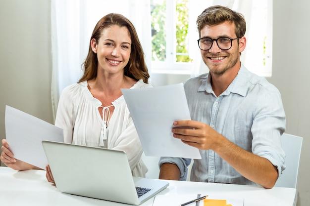 Портрет мужских и женских коллег, обсуждая документ в офисе