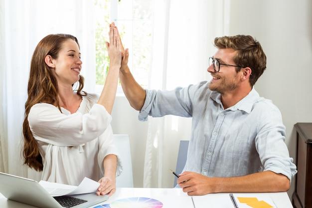Коллеги дают высокие пять на офисном столе