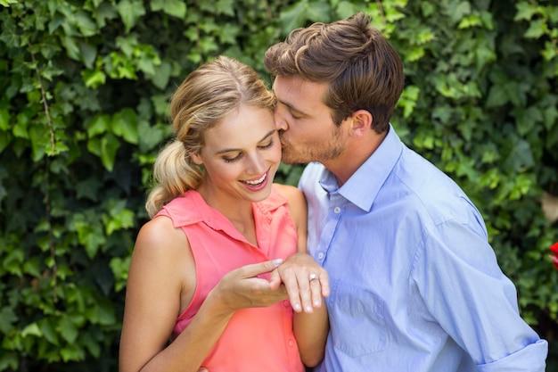 Романтический мужчина целует женщину на переднем дворе
