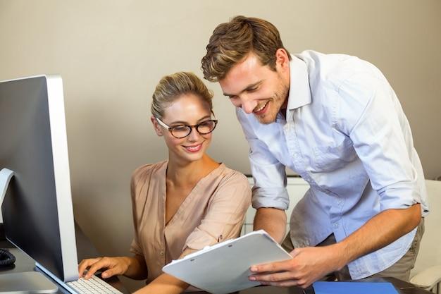 オフィスで書類を議論する若い同僚