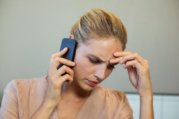 Разочарованная женщина разговаривает по телефону