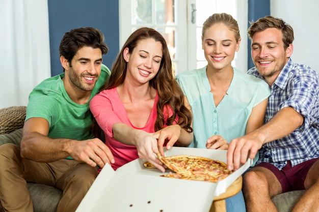 家でピザを食べて幸せな友達