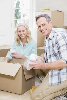 Улыбающаяся пара упаковывает кружку в коробку дома