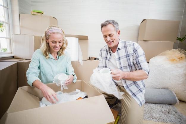自宅でボックスに笑顔のカップル梱包マグカップ