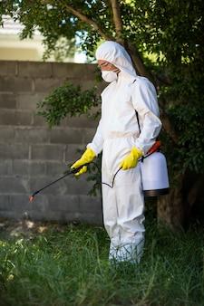 草に殺虫剤を散布する男