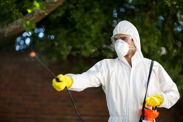 木に対して立っている間殺虫剤を使用している人