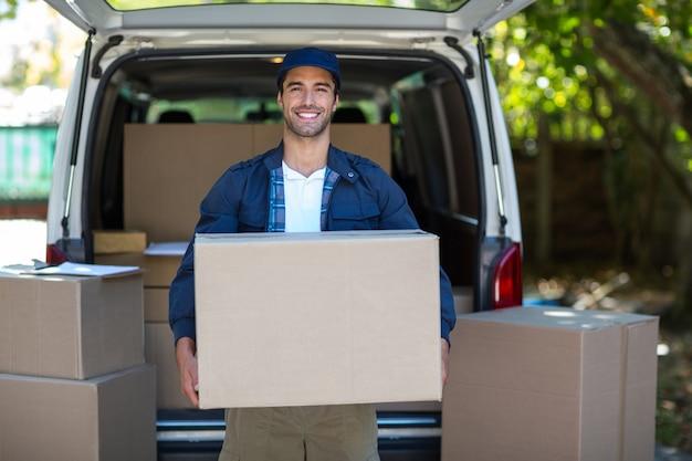 Портрет улыбающегося доставщика, несущего картонную коробку