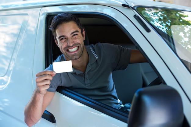 空白のカードを示す歯を見せる笑顔でハンサムなドライバー