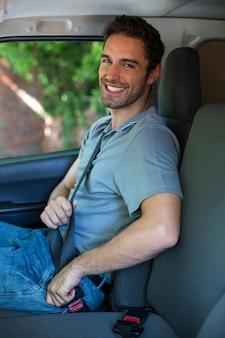ハンサムなドライバーが車のシートベルトを締める