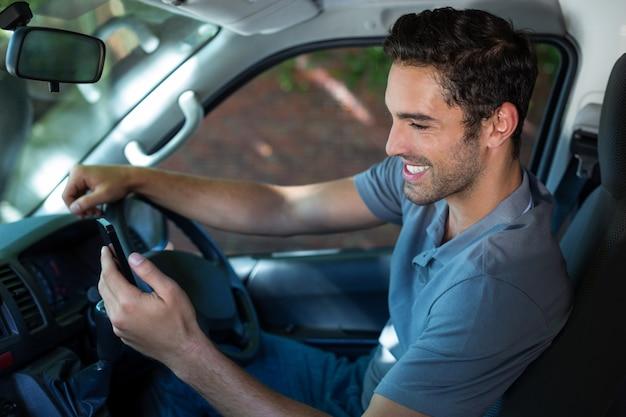 Водитель с помощью телефона, сидя в машине