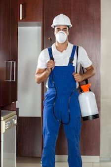 キッチンで害虫駆除をしている男