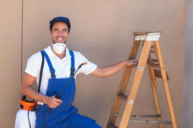 はしごで立っている農薬労働者の肖像