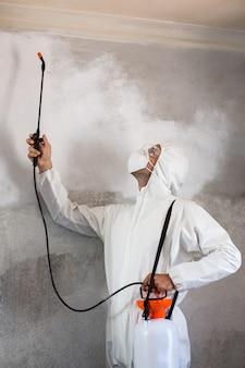 壁に害虫スプレーを使用して肉体労働者