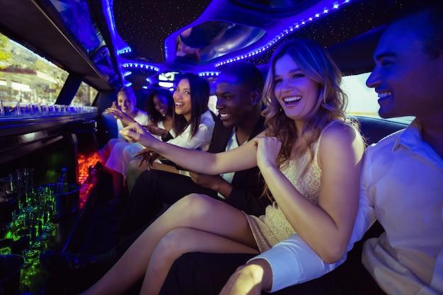 Счастливые друзья общаются в лимузине