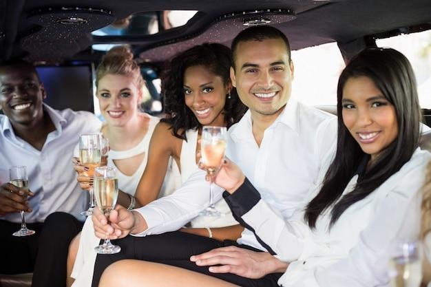 Хорошо одетые люди пьют шампанское в лимузине