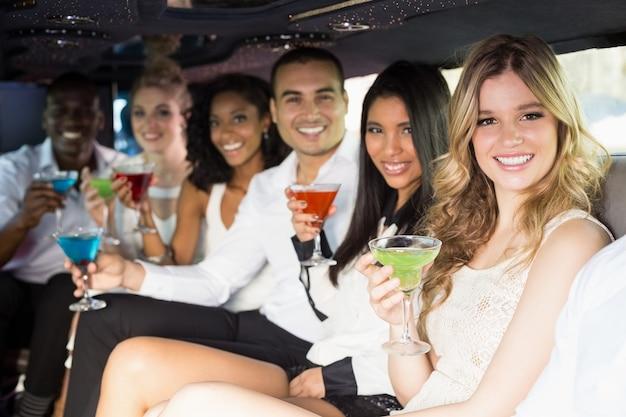 Хорошо одетые люди пьют коктейли в лимузине
