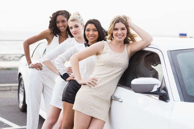 Хорошо одетые женщины позируют, опираясь на лимузин