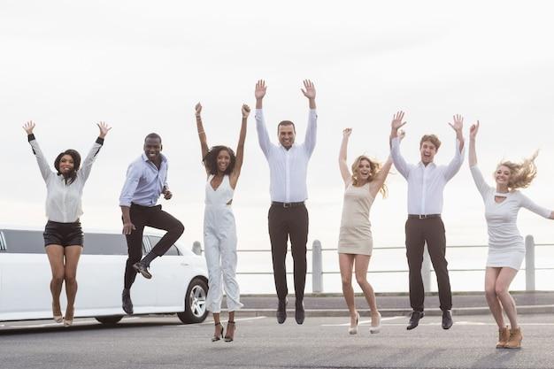 Хорошо одетые люди прыгают рядом с лимузином