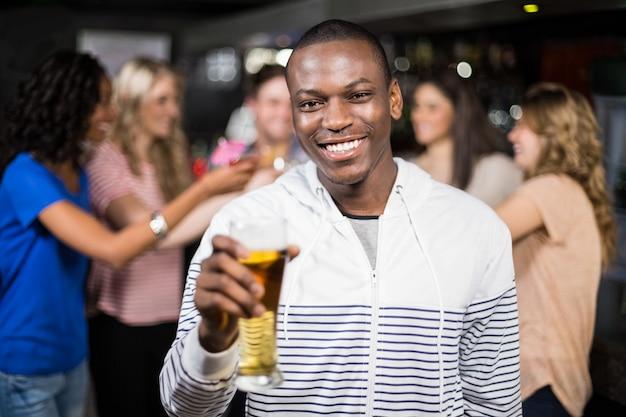 Улыбающийся человек показывает пиво со своими друзьями