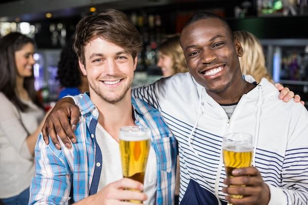 Улыбающиеся друзья, показывающие пиво со своими друзьями