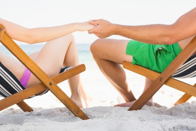 手を繋いでいるデッキチェアに座っているカップル