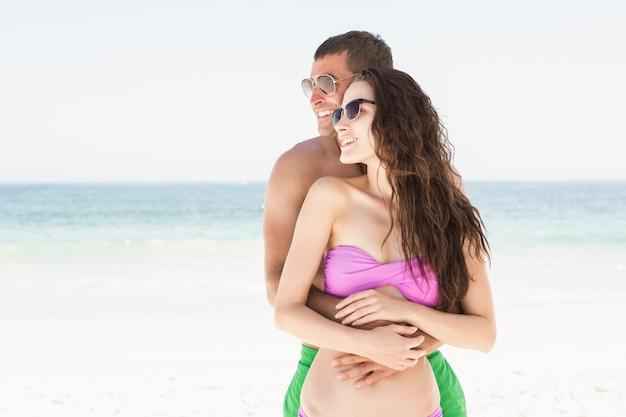 笑顔のカップルがビーチでハグ