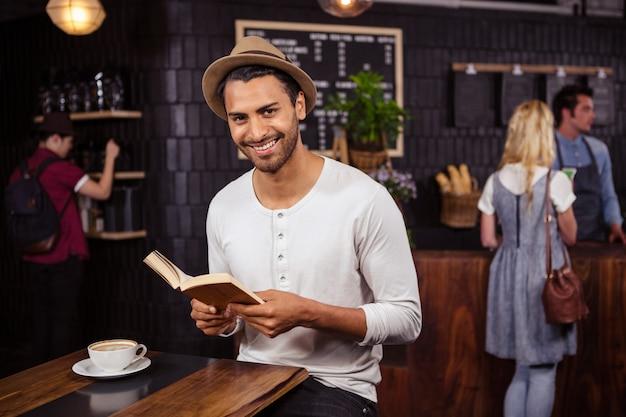 Мужчина читает книгу и улыбается