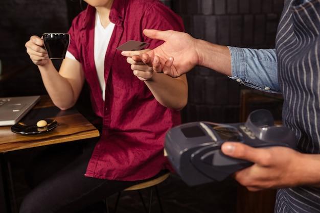 Мужчина платит кофе кредитной картой