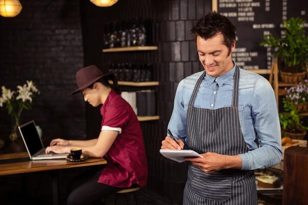 Официант записывает заказы
