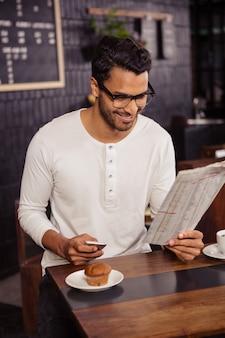 スマートフォンと新聞を持つ男
