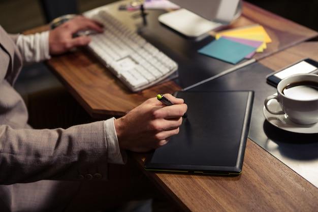 コンピューターとグラフィックタブレットを使用して創造的なビジネスマン