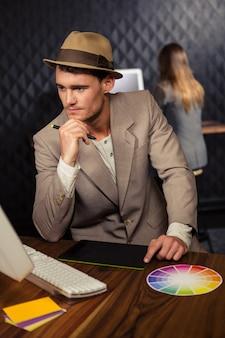 Творческий бизнесмен, используя компьютер и графический планшет