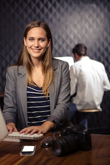 Творческая коммерсантка используя компьютер