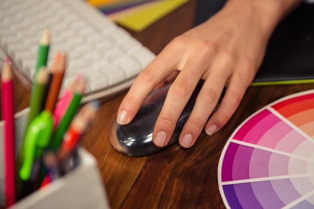コンピューターのマウスを使用して女性の手のクローズアップ