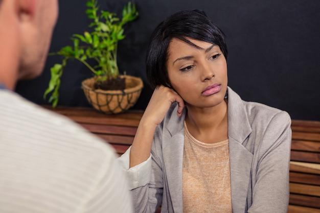 彼女のボーイフレンドの前に座っている不幸な女性