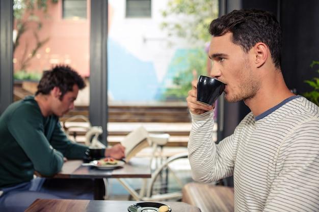 思いやりのある男がコーヒーを飲む