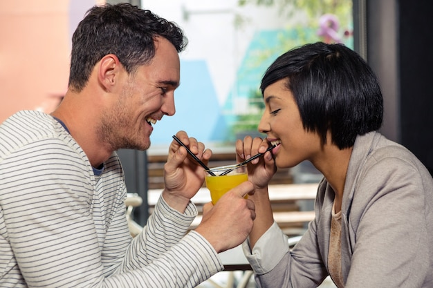 オレンジジュースを一緒に飲むかわいいカップル