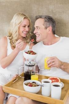 かわいいカップルが彼らの部屋でベッドで朝食をとります。