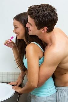 Пара обнимает во время чистки зубов